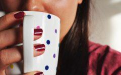 Motywacja, kubek w kolorowe groszki, czerwone paznokcie