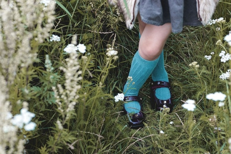 Łąka, stokrotki, buciki, niebieskie skarpetki