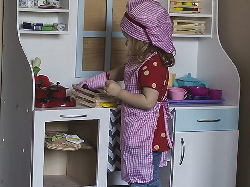 Drewniana kuchnia w pokoju dwulatki, biało-niebieska, z plastikowymi naczyniami.