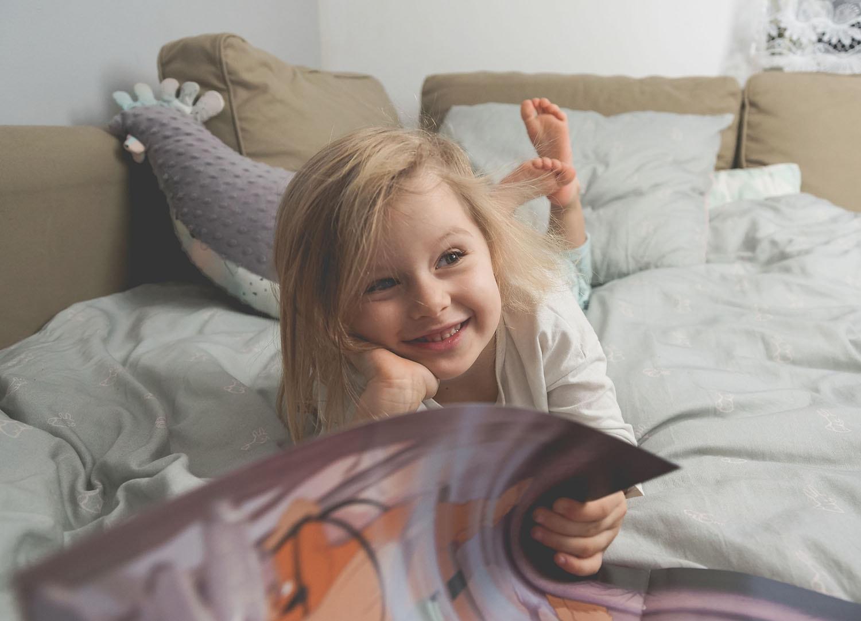 Jak nauczyć dziecko czytać książki? Urocze zdjęcie dziewczynki trzymającej stronę, patrzącej nie na nią, a przez nią - najpewniej na swoją mamę