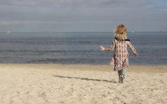Ostatni ciepły weekend nad morzem - dziecko spoglądające na wodę w różowej sukience