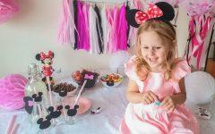 Wymarzone urodziny dla dzieci - dziecko z opaską z uszkami Myszki Minnie, obok kubeczki z wzorem z Myszką Minnie i słomki